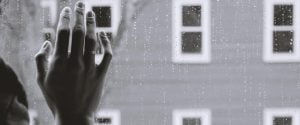 Person holding hand on window in rain